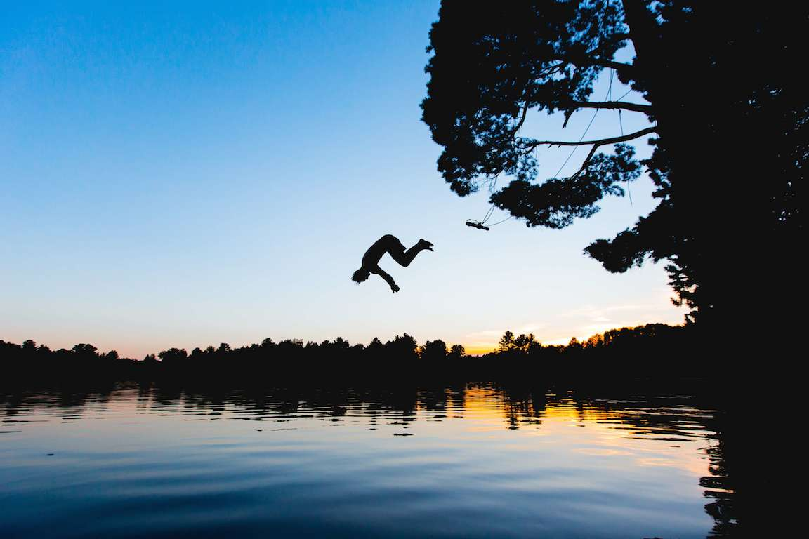 diving into a lake off a swing while sun sets